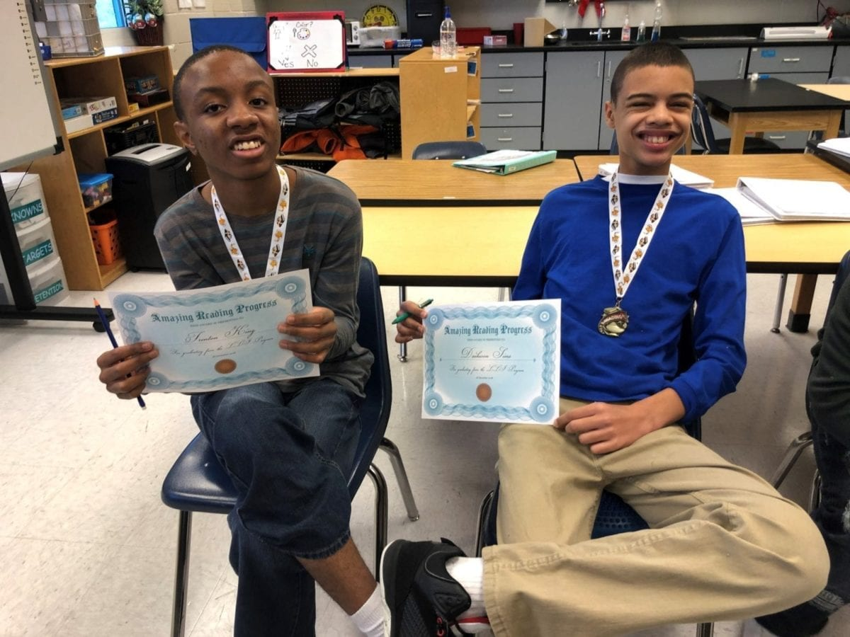 Two students celebrating their reading accomplishments