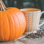 Pumpkin next to a cup of coffee